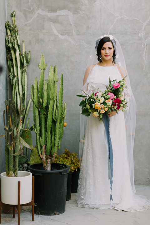 Los angeles outdoor colorful wedding bride a line gown with a high neckline and open shoulder lace sleeves with long veil and lace detail holding colorful floral bridal bouquet with long blue ribbon