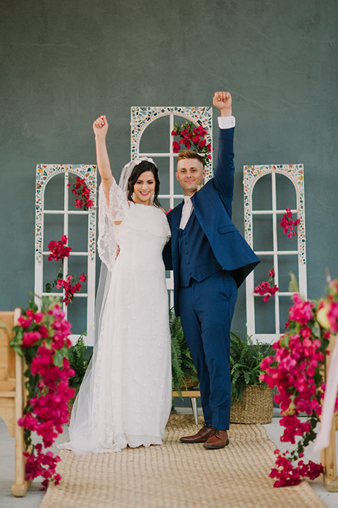 Los angeles outdoor colorful wedding bride a line gown with a high neckline and open shoulder lace sleeves and groom cobalt blue notch lapel suit by allure men with a matching vest and white dress shirt with a long white matte tie and white floral boutonniere cheering after ceremony