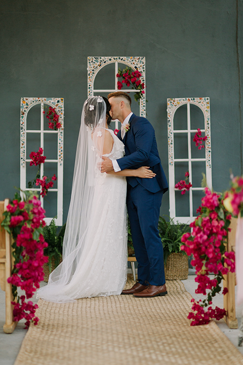 Los angeles outdoor colorful wedding bride a line gown with a high neckline and open shoulder lace sleeves and groom cobalt blue notch lapel suit by allure men with a matching vest and white dress shirt with a long white matte tie and white floral boutonniere kissing during ceremony