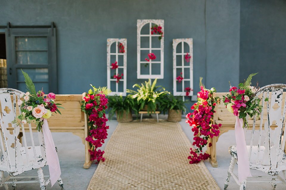Los angeles outdoor colorful wedding at city libre ceremony set up with light brown wood aisle and wooden benches with white chairs and bright pink florals and white window pane decor on wall wedding photo idea for ceremony set up