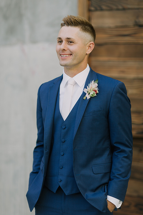 Los angeles outdoor colorful wedding at city libre groom cobalt blue notch lapel suit by allure men with a matching vest and a white dress shirt with a long white matte tie and white floral boutonniere standing with hands in pockets close up