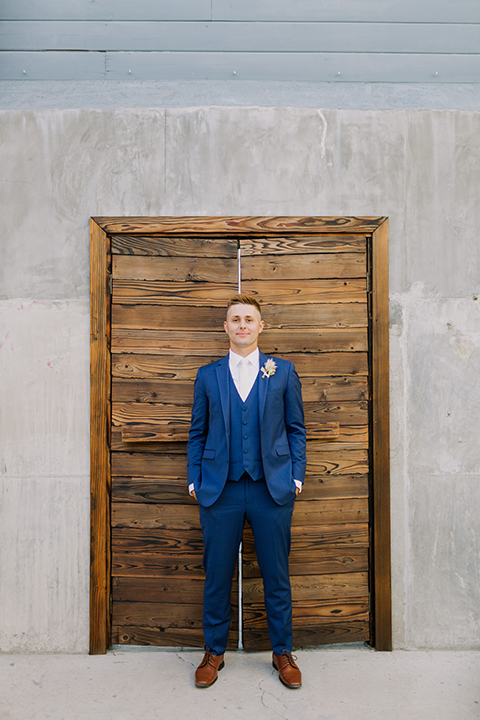 Los angeles outdoor colorful wedding at city libre groom cobalt blue notch lapel suit by allure men with a matching vest and a white dress shirt with a long white matte tie and white floral boutonniere standing with hands in pockets