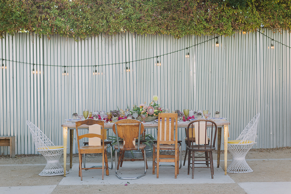 Los angeles outdoor colorful wedding at city libre table set up light brown wood table with an assortment of different style wooden chairs and flower centerpiece decor with white and blue place settings and colorful glassware