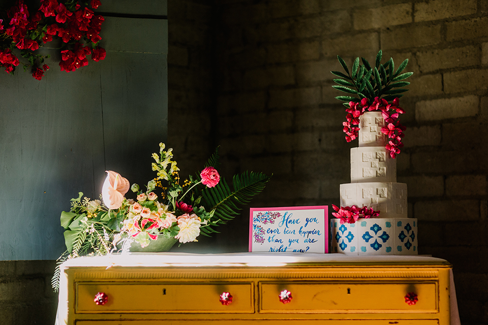 Los angeles outdoor colorful wedding at city libre wedding dessert table set up light brown wooden table with drawers and four tier white and blue wedding cake with bright pink florals on top with calligraphy sign and flower decor on top of table wedding photo idea for dessert table and wedding cake