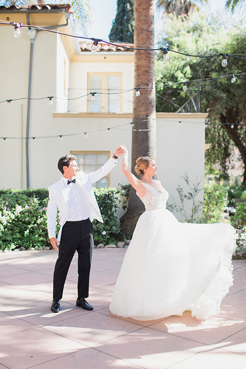 Pasadena outdoor wedding at the maxwell house bride mermaid style gown with thin spaghetti straps and beaded detail with a sweetheart neckline and groom white dinner jacket with black tuxedo pants and a white dress shirt with a black bow tie dancing and twirling bride