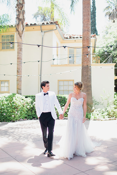 Pasadena outdoor wedding at the maxwell house bride mermaid style gown with thin spaghetti straps and beaded detail with a sweetheart neckline and groom white dinner jacket with black tuxedo pants and a white dress shirt with a black bow tie holding hands and walking