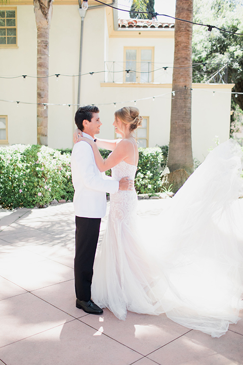 Pasadena outdoor wedding at the maxwell house bride mermaid style gown with thin spaghetti straps and beaded detail with a sweetheart neckline and groom white dinner jacket with black tuxedo pants and a white dress shirt with a black bow tie hugging and smiling