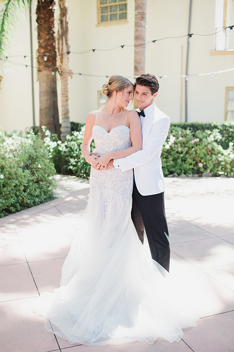 Pasadena outdoor wedding at the maxwell house bride mermaid style gown with thin spaghetti straps and beaded detail with a sweetheart neckline and groom white dinner jacket with black tuxedo pants and a white dress shirt with a black bow tie hugging