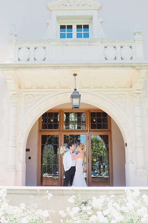 Pasadena outdoor wedding at the maxwell house bride mermaid style gown with thin spaghetti straps and beaded detail with a sweetheart neckline and groom white dinner jacket with black tuxedo pants and a white dress shirt with a black bow tie hugging far away