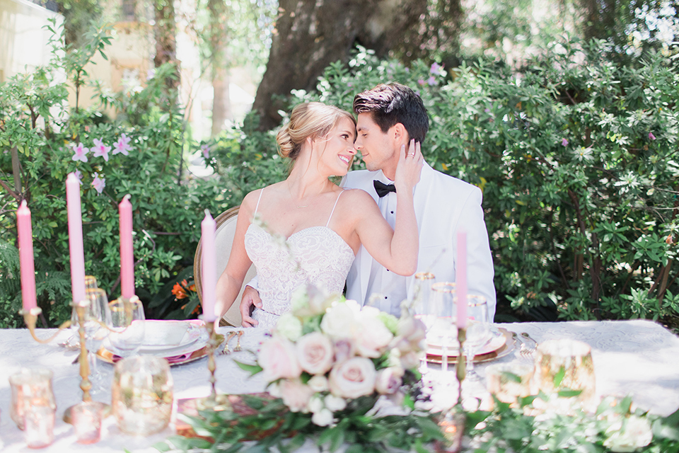 Pasadena outdoor wedding at the maxwell house bride mermaid style gown with thin spaghetti straps and beaded detail with a sweetheart neckline and groom white dinner jacket with black tuxedo pants and a white dress shirt with a black bow tie sitting by table hugging