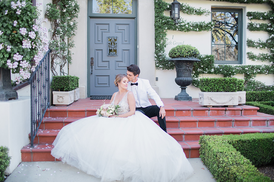 Pasadena outdoor wedding at the maxwell house bride mermaid style gown with thin spaghetti straps and beaded detail with a sweetheart neckline and groom white dinner jacket with black tuxedo pants and a white dress shirt with a black bow tie sitting on steps smiling