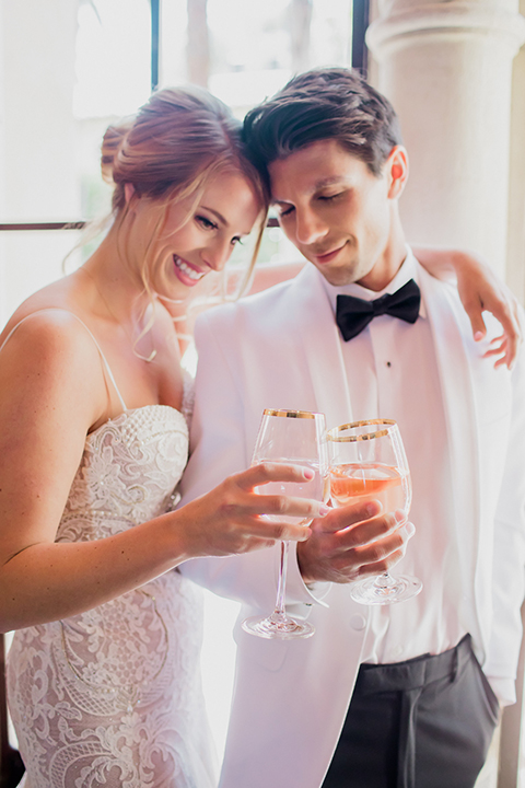 Pasadena outdoor wedding at the maxwell house bride mermaid style gown with thin spaghetti straps and beaded detail with a sweetheart neckline and groom white dinner jacket with black tuxedo pants and a white dress shirt with a black bow tie standing and hugging holding drinks