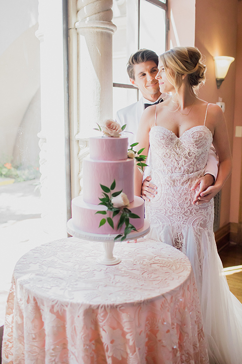 Pasadena outdoor wedding at the maxwell house bride mermaid style gown with thin spaghetti straps and beaded detail with a sweetheart neckline and groom white dinner jacket with black tuxedo pants and a white dress shirt with a black bow tie standing by cake hugging