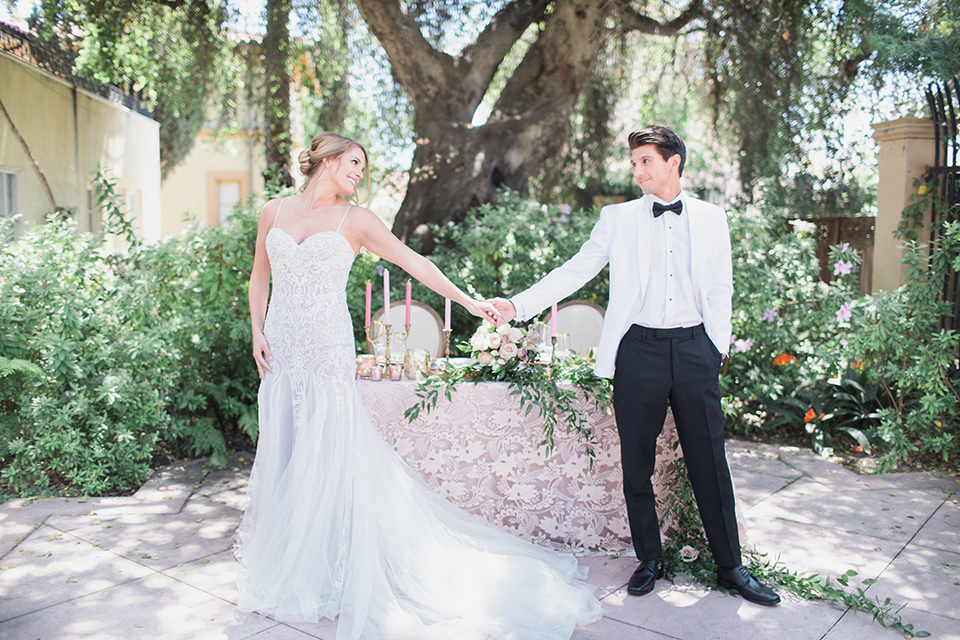 Pasadena outdoor wedding at the maxwell house bride mermaid style gown with thin spaghetti straps and beaded detail with a sweetheart neckline and groom white dinner jacket with black tuxedo pants and a white dress shirt with a black bow tie standing by table holding hands