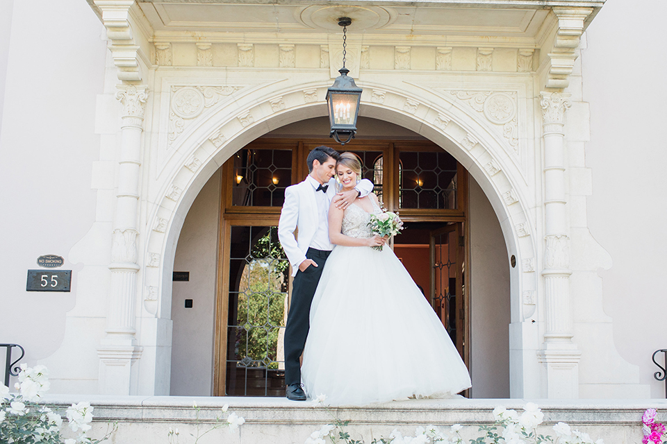 Pasadena outdoor wedding at the maxwell house bride mermaid style gown with thin spaghetti straps and beaded detail with a sweetheart neckline and groom white dinner jacket with black tuxedo pants and a white dress shirt with a black bow tie standing on ledge hugging