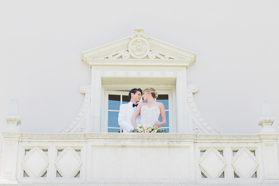 Pasadena outdoor wedding at the maxwell house bride mermaid style gown with thin spaghetti straps and beaded detail with a sweetheart neckline and groom white dinner jacket with black tuxedo pants and a white dress shirt with a black bow tie standing on balcony hugging