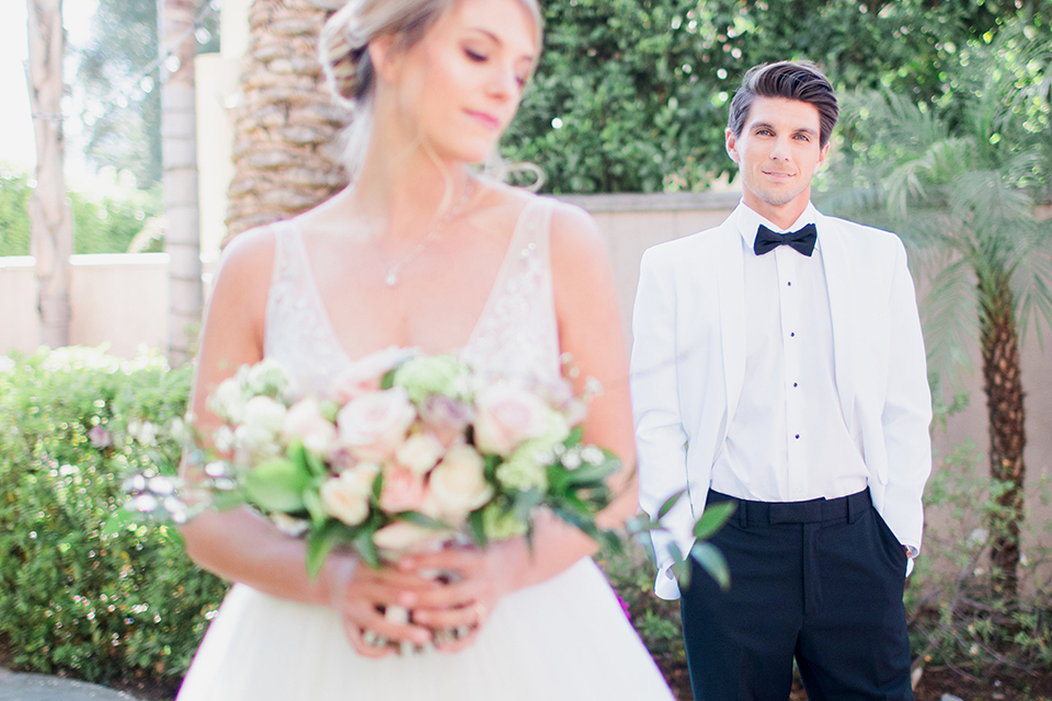 Pasadena outdoor wedding at the maxwell house bride mermaid style gown with thin spaghetti straps and beaded detail with a sweetheart neckline and groom white dinner jacket with black tuxedo pants and a white dress shirt with a black bow tie standing smiling