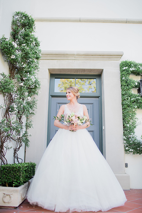 Pasadena outdoor wedding at the maxwell house bride ball gown with straps and a plunging neckline with beaded detail holding white and green floral bridal bouquet