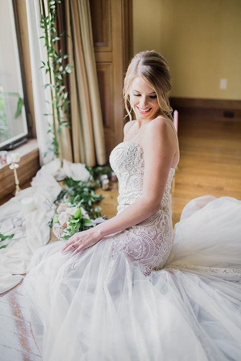 Pasadena outdoor wedding at the maxwell house bride form fitting mermaid style gown with thin spaghetti straps and beaded detail sitting on ground with candle decor close up