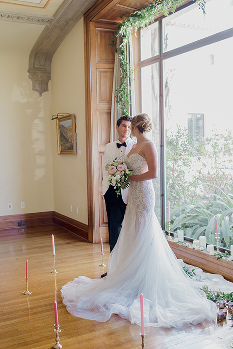 Pasadena outdoor wedding at the maxwell house bride mermaid style gown with thin spaghetti straps and beaded detail with a sweetheart neckline and groom white dinner jacket with black tuxedo pants and a white dress shirt with a black bow tie holding hands during ceremony