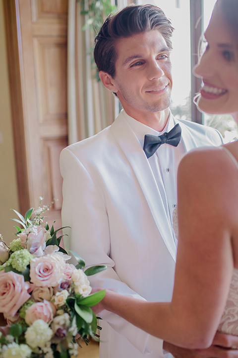 Pasadena outdoor wedding at the maxwell house bride mermaid style gown with thin spaghetti straps and beaded detail with a sweetheart neckline and groom white dinner jacket with black tuxedo pants and a white dress shirt with a black bow tie hugging during ceremony close up