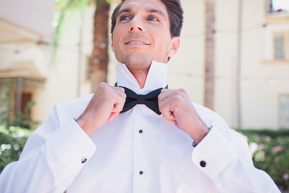 Pasadena outdoor wedding at the maxwell house groom white dinner jacket with black tuxedo pants and a white dress shirt with a black bow tie getting ready holding bow tie
