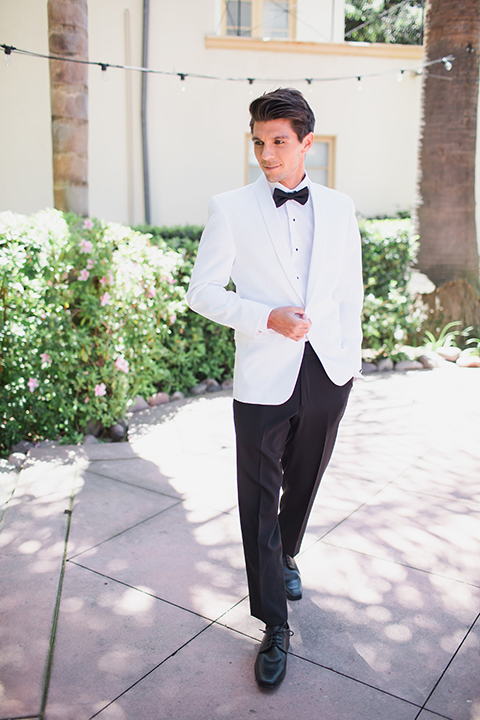 Pasadena outdoor wedding at the maxwell house groom white dinner jacket with black tuxedo pants and a white dress shirt with a black bow tie holding jacket