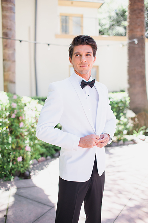 Pasadena outdoor wedding at the maxwell house groom white dinner jacket with black tuxedo pants and a white dress shirt with a black bow tie buttoning jacket