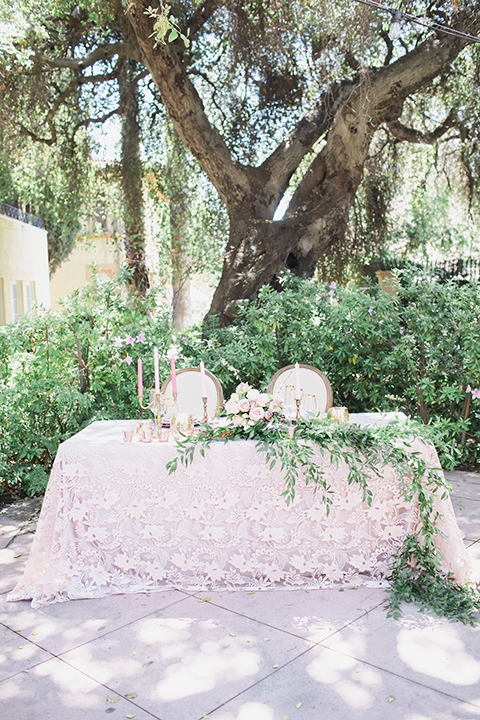Pasadena outdoor wedding at the maxwell house table set up blush pink lace table linen with greenery floral decor and white vintage chairs with candles and flower centerpieces