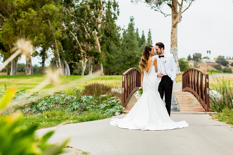Southern california outdoor wedding at diamond bar golf course bride form fitting mermaid style gown with silver beaded straps and a sweetheart neckline with a low back design and beaded detail with groom white notch lapel dinner jacket with a white dress shirt and black tuxedo pants with a black bow tie hugging