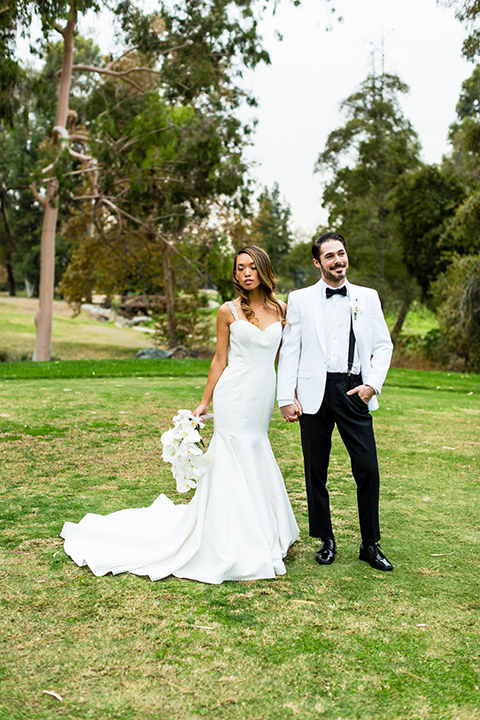 Southern california outdoor wedding at diamond bar golf course bride form fitting mermaid style gown with silver beaded straps and a sweetheart neckline with a low back design and beaded detail with groom white notch lapel dinner jacket with a white dress shirt and black tuxedo pants with a black bow tie hugging and bride holding white and green floral bridal bouquet