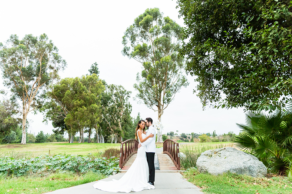 Southern california outdoor wedding at diamond bar golf course bride form fitting mermaid style gown with silver beaded straps and a sweetheart neckline with a low back design and beaded detail with groom white notch lapel dinner jacket with a white dress shirt and black tuxedo pants with a black bow tie hugging far away