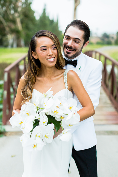 Southern california outdoor wedding at diamond bar golf course bride form fitting mermaid style gown with silver beaded straps and a sweetheart neckline with a low back design and beaded detail with groom white notch lapel dinner jacket with a white dress shirt and black tuxedo pants with a black bow tie hugging close up and bride holding white and green floral bridal bouquet