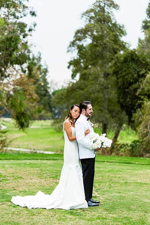 Southern california outdoor wedding at diamond bar golf course bride form fitting mermaid style gown with silver beaded straps and a sweetheart neckline with a low back design and beaded detail with groom white notch lapel dinner jacket with a white dress shirt and black tuxedo pants with a black bow tie bride hugging groom behind and groom holding white and green floral bridal bouquet