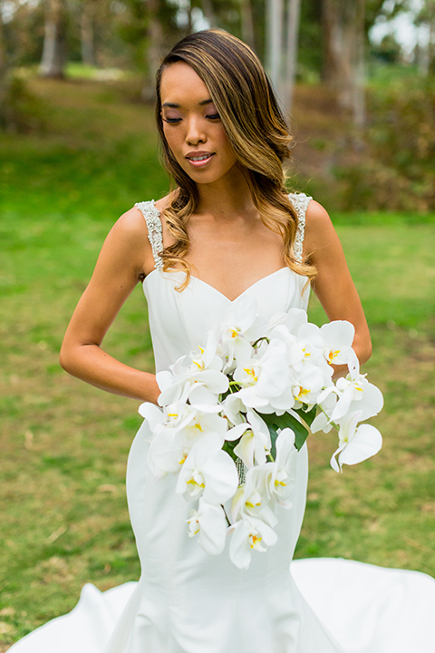 Southern california outdoor wedding at diamond bar golf course bride form fitting mermaid style gown with silver beaded straps and a sweetheart neckline with a low back design and beaded detail with white and green floral bridal bouquet close up
