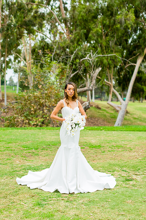 Southern california outdoor wedding at diamond bar golf course bride form fitting mermaid style gown with silver beaded straps and a sweetheart neckline with a low back design and beaded detail with white and green floral bridal bouquet
