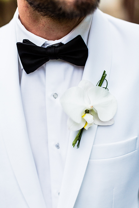 Southern california outdoor wedding at diamond bar golf course groom white notch lapel dinner jacket with a white dress shirt and black tuxedo pants with a black bow tie and white floral boutonniere close up