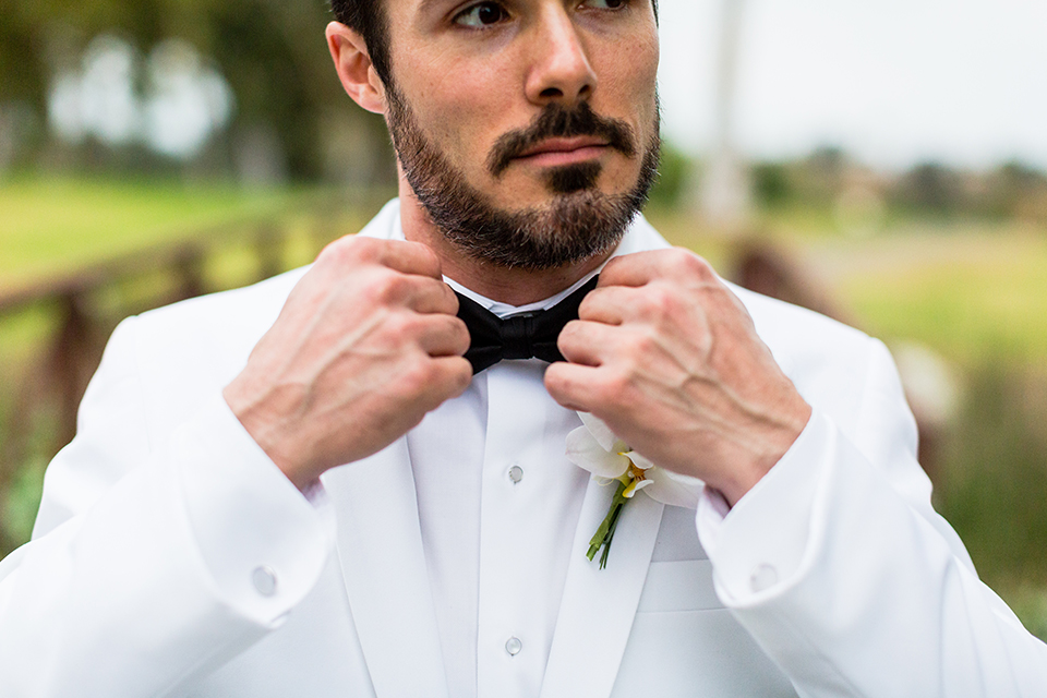 Southern california outdoor wedding at diamond bar golf course groom white notch lapel dinner jacket with a white dress shirt and black tuxedo pants with a black bow tie and white floral boutonniere holding bow tie