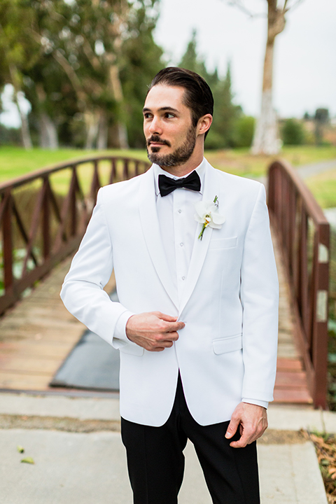 Southern california outdoor wedding at diamond bar golf course groom white notch lapel dinner jacket with a white dress shirt and black tuxedo pants with a black bow tie and white floral boutonniere holding jacket