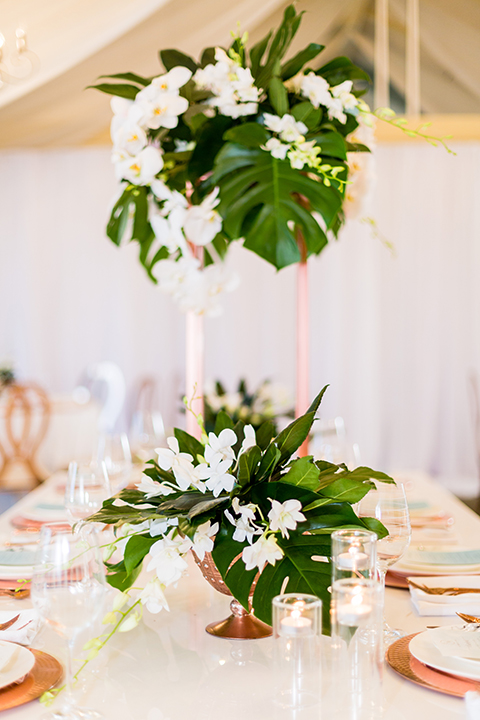 Southern california outdoor wedding at diamond bar golf course table set up white table with greenery floral decor and rose gold chairs with hanging decor and wall with greenery florals and white and gold place settings with gold silverware