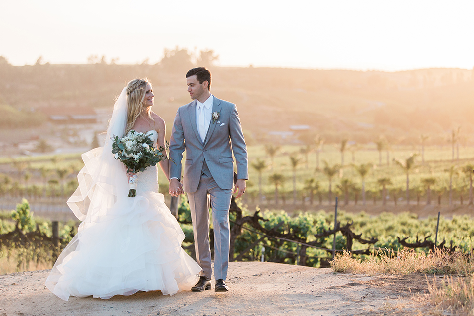 Temecula outdoor wedding at falkner winery bride mermaid style gown with lace bodice and sweetheart neckline with ruffled skirt and long veil holding white and green floral bridal bouquet in vineyard holding hands and walking