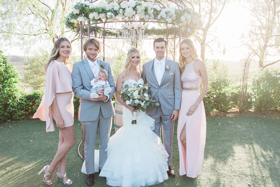 Temecula outdoor wedding at falkner winery bride mermaid style gown with lace bodice and sweetheart neckline with ruffled skirt and long veil holding white and green floral bridal bouquet standing with family smiling