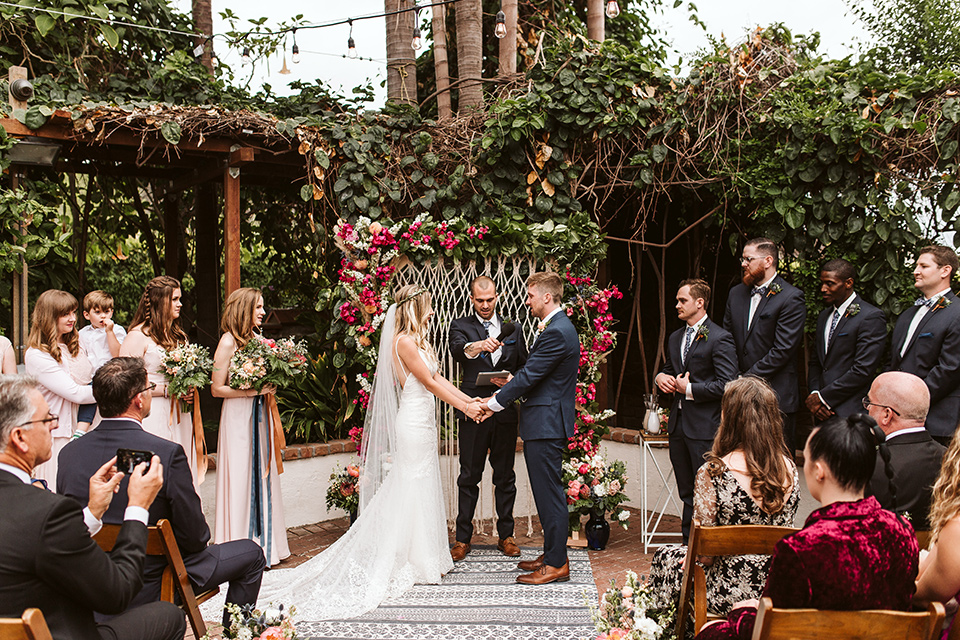 Adobe-de-Capastrano-Amanda-and-Asher-at-ceremony-holding-hands-bride-wearing-a-white-lace-fit-and-flare-gown-with-open-back-and-sweetheart-neckline-groom-in-navy-suit-with-blue-and-white-floral-tie