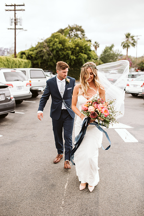 Adobe-de-Capastrano-Amanda-and-Asher-bride-and-groom-in-parkinglot-bride-wearing-a-white-lace-fit-and-flare-gown-with-open-back-and-sweetheart-neckline-groom-in-navy-suit-with-blue-and-white-floral-tie-and-brown-shoes-holding-u-her-dress-so-it-does-not-get-dirty