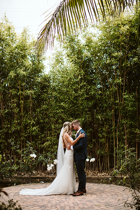 Adobe-de-Capastrano-Amanda-and-Asher-bride-and-groom-touching-heads-with-bamboo-behind-them-bride-wearing-a-white-lace-fit-and-flare-gown-with-open-back-and-sweetheart-neckline-groom-in-navy-suit-with-blue-and-white-floral-tie-and-brown-shoes