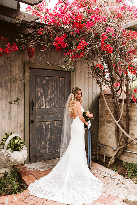 Adobe-de-Capastrano-Amanda-and-Asher-bride-standing-by-wooden-door-looking-over-her-shoulder-and-down-bride-wearing-a-white-lace-fit-and-flare-gown-with-open-back-and-sweetheart-wearing-a-green-floral-crown-with-hair-in-loose-waves-standing-by-a-wooden-door-holding-her-bouquette