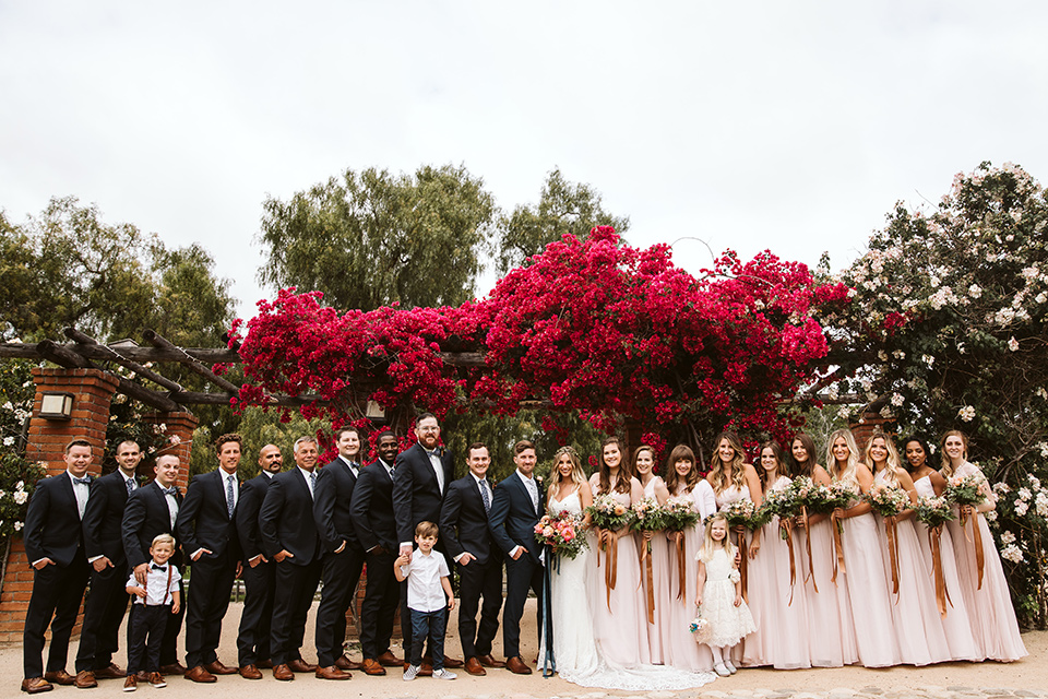 Adobe-de-Capastrano-Amanda-and-Asher-entire-bridal-party-the-bridesmaids-wearing-flowing-blush-colored-dresses-in-all-different-styles-and-necklines-groomsmen-wearing-navy-suits-with-floral-ties-and-brown-shoes-bride-wearing-a-white-lace-fit-and-flare-gown-with-open-back-and-sweetheart-neckline-groom-in-navy-suit-with-blue-and-white-floral-tie