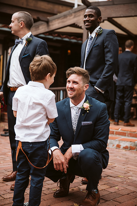 Adobe-de-Capastrano-Amanda-and-Asher-groom-and-ringbarer-groom-in-navy-suit-with-blue-and-white-floral-tie-and-brown-shoes