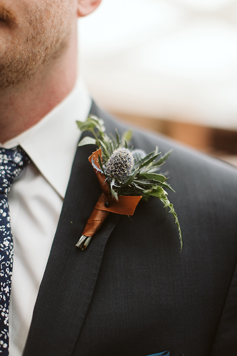 Adobe-de-Capastrano-Amanda-and-Asher-groom-close-up-on-boutionneire-groom-wearing-a-navy-suit-and-floral-tie-with-succulent-boutonniere