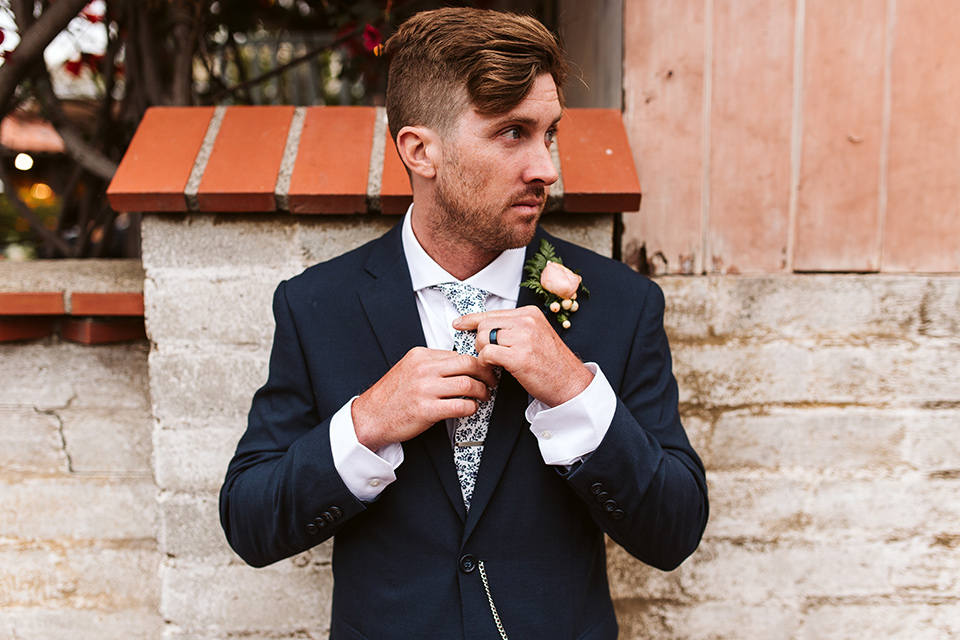 Adobe-de-Capastrano-Amanda-and-Asher-groom-fixing-tie-looking-to-the-left-groom-in-navy-suit-with-blue-and-white-floral-tie